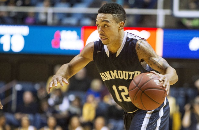 Monmouth guard Justin Robinson (12) brings the ball up court during an NCAA college basketball game against West Virginia, Friday, Nov. 14, 2014, in Morgantown, W.Va. (AP Photo/Raymond Thompson)